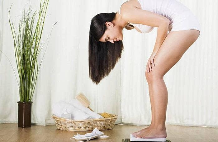 Девушка смотрит свой вес