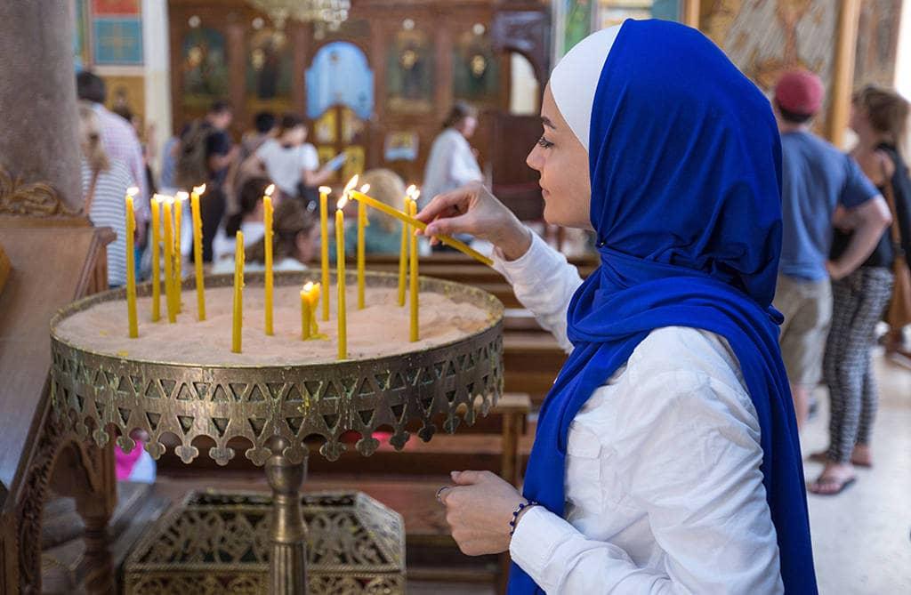 Девушка ставить свечку в церкви